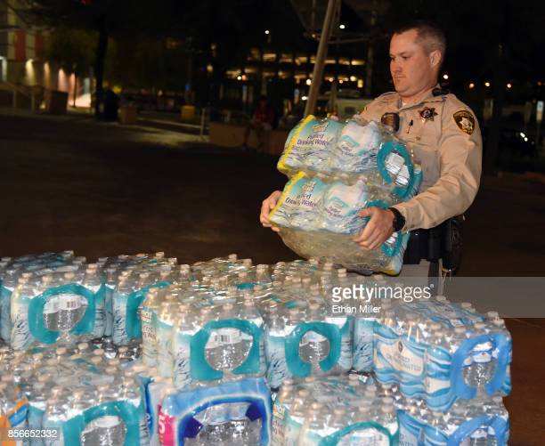 Las Vegas Metropolitan Police Department officer helps deliver bottled water to people at the Thomas Mack Center after a mass shooting at a country...