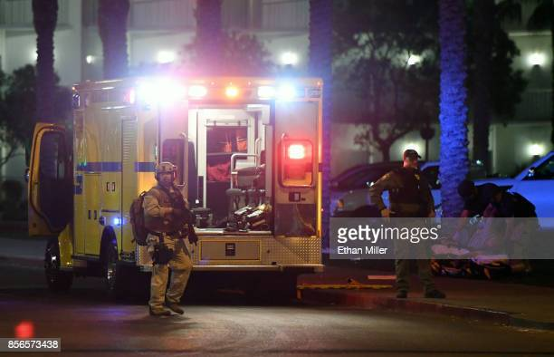 Las Vegas Metropolitan Police Department officers stand near an ambulance as medical personnel treat a person in the parking lot of the Hooters...