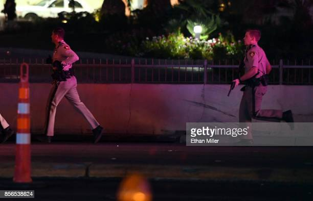 Las Vegas Metropolitan Police officers run down Tropicana Ave near Las Vegas Boulevard after a mass shooting at a country music festival nearby on...