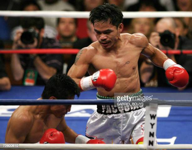 Manny Pacquiao of the Philippines looks at Erik Morales of Mexico as he goes down due to knockout during their WBC International Super Featherweight...