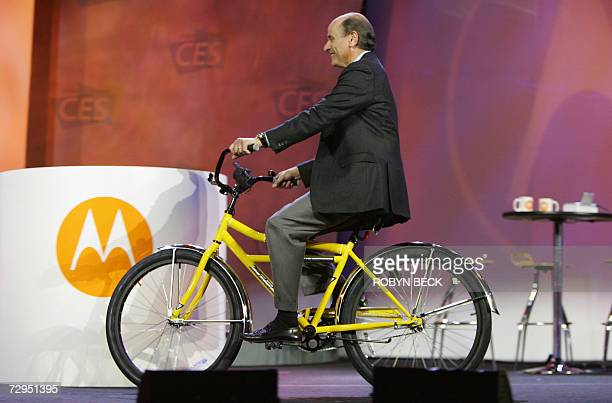 Motorola CEO Ed Zander rides a bicycle with a handlebarmounted cell phone charger as he takes the stage at the start of his keynote address at the...