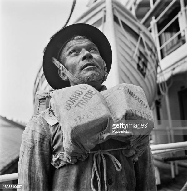 Lascar bosun seaman, wearing a life jacket, stands on board the hospital ship HMS Vasna at port in England during World War II on 11th July 1941.