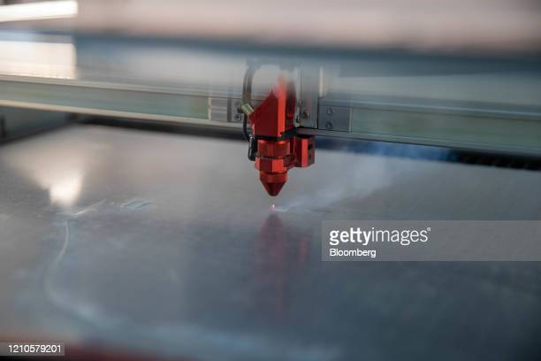 Laser cutter cuts out a protective face shield at JK Automotive in Stoneham, Massachusetts, U.S., on Monday, April 20, 2020. JK Automotive and the...