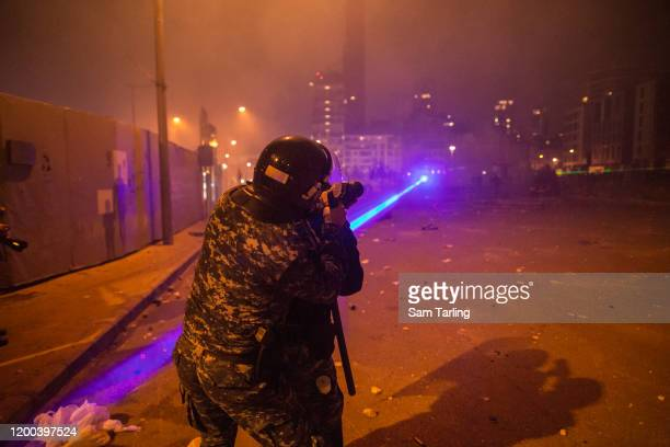 Laser is aimed at riot police as they fire tear gas at a large group of anti-government protesters, on January 18 in Beirut, Lebanon. According to...