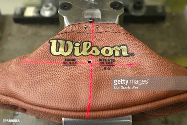 A laser is used to line up stamps that apply the AFC and NFC champion team names on footballs for the Super Bowl at the Wilson football factory...