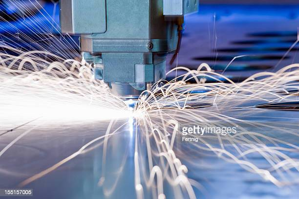 CNC laser metal-cutting tool in operation with sparks