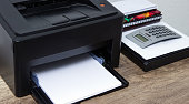 Laser printer and office supplies on the table.