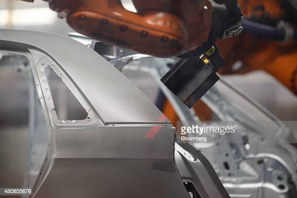 Laser sensors scan the body shell of an Audi A1 automobile for faults during manufacture on the production line at the Audi AG factory in Vorst...