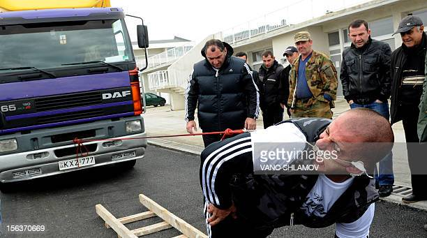 Lasha Pataraia pulls an eightton truck with his ear during a test event in the Georgian city of Rustavi outside Tbilisi on November 14 2012 The...