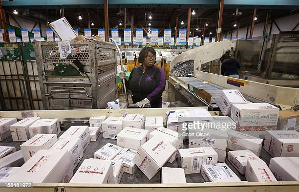 Lashaun Kerby moves mail on a conveyor at the United States Postal Service Chicago Logistics and Distribution Center on December 17 2012 in Elk Grove...