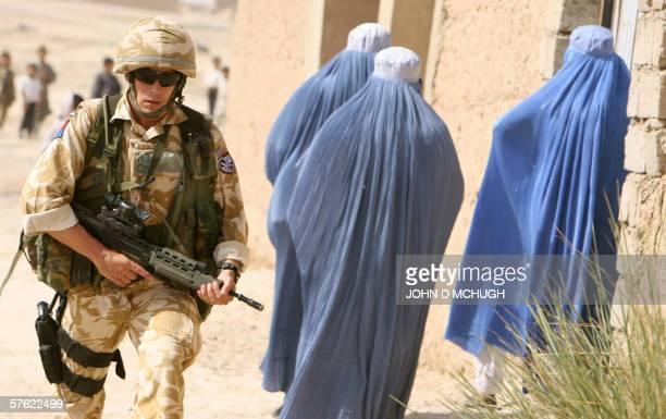 A British soldier from 16 Air Assault Brigade walks past three women wearing burkas during a foot patrol in Lashkar Gah Helmand province 16 May 2006...