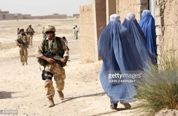 A British soldier from 16 Air Assault Brigade walks past three women wearing burkas during a foot patrol in Lashkar Gah Helmand province 16 May 2006...