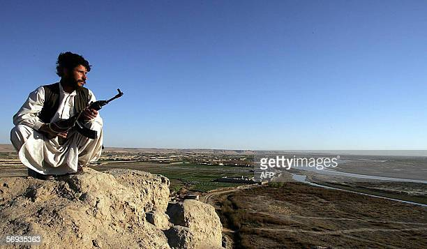An Afghani policeman looks out to the horizon whilst on patrol in the mountains surrounding the Helmand Rver valley in southern Afghanistan 24...