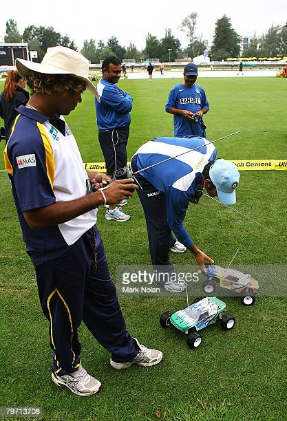 Lasith Malinga of Sri Lanka and MS Dhoni of India play with a remote control car as rain delays play before the Commonealth Bank Series One Day...