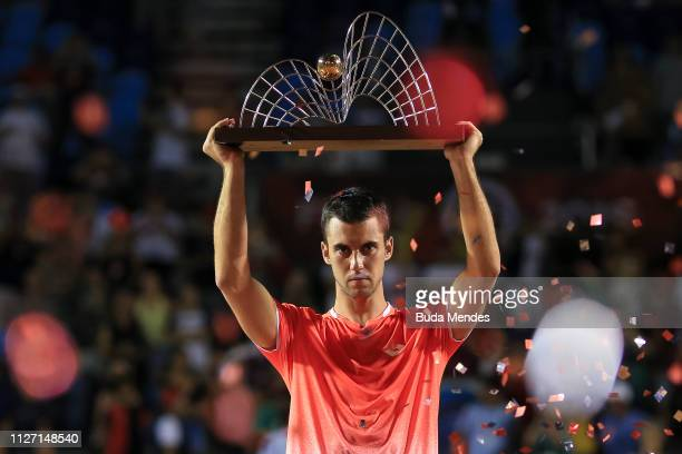 Laslo Djere of Serbia celebrates with the trophy after defeating Felix Auger-Aliassime of Canada at the singles final of the ATP Rio Open 2019 at...