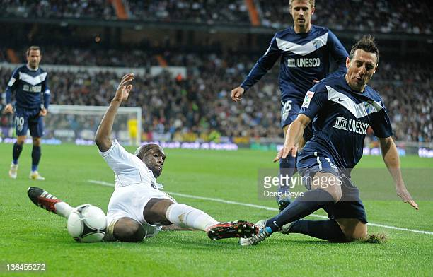 Lass Diarra of Real Madrid is tackled by Santiago Cazorla of Malaga during the round of 16 Copa del Rey first leg match between Real Madrid and...