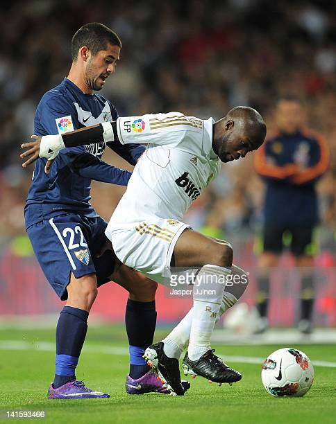 Lassana Diarra of Real Madrid duels for the ball with Francisco Suarez of Malaga during the la Liga match between Real Madrid CF and Malaga CF at the...