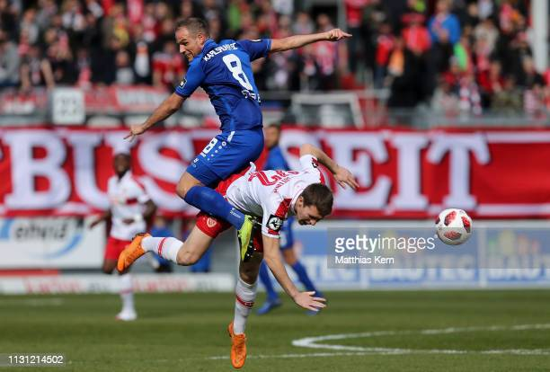 Lasse Schlueter of Cottbus jumps for the ball with Manuel Stiefler of Karlsruhe during the 3 Liga match between FC Energie Cottbus and Karlsruher SC...