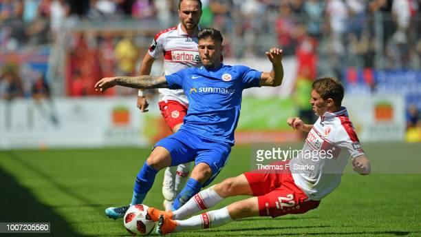 Lasse Schlueter of Cottbus tackles Vladimir Rankovic of Rostock during the 3. Liga match between FC Energie Cottbus and F.C. Hansa Rostock at Stadion...
