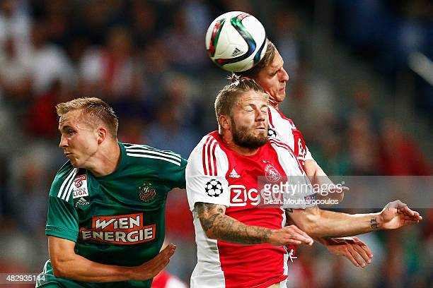 Lasse Schone and Arkadiusz Milik of Ajax challenges for the headed ball with Christopher Dibon of Rapid Wien during the third qualifying round 2nd...