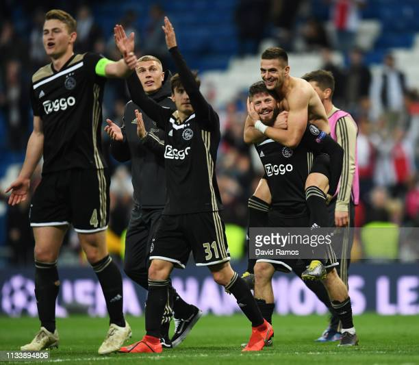 Lasse Schone and Dusan Tadic of Ajax celebrate victory with team matesafter the UEFA Champions League Round of 16 Second Leg match between Real...