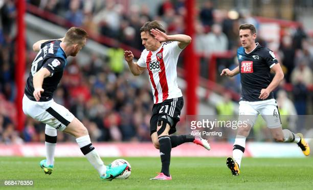 Lasse Vibe of Brentford is chased by Craig Bryson of Derby County and Alex Pearce of Derby County during the Sky Bet Championship match between...