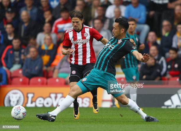 Lasse Vibe of Brentford is tackled by Maya Yoshida of Southampton during the Pre Season Friendly match between Brentford and Southampton at Griffin...