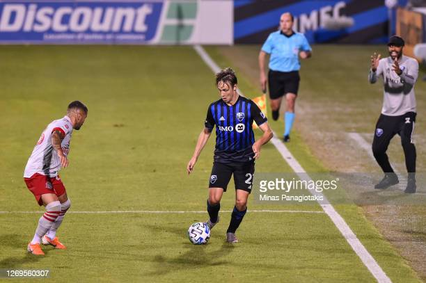 Lassi Lappalainen of the Montreal Impact controls the ball against Auro Jr #96 of Toronto FC while Montreal Impact head coach Thierry Henri reacts...