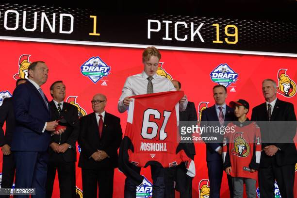 Lassi Thomson puts on a jersey after being selected nineteenth overall by the Ottawa Senators during the first round of the 2019 NHL Draft at Rogers...