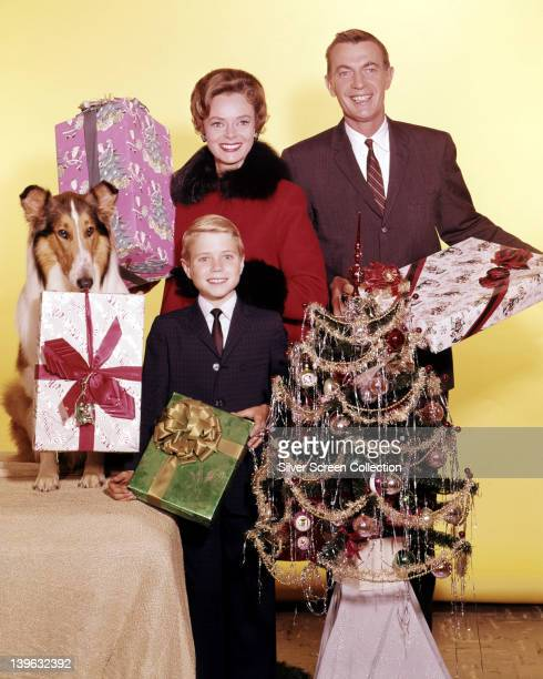 Lassie with Jon Provost US child actor June Lockhart US actress and Hugh Reilly US actor pose for a group studio portrait holding giftwrapped...