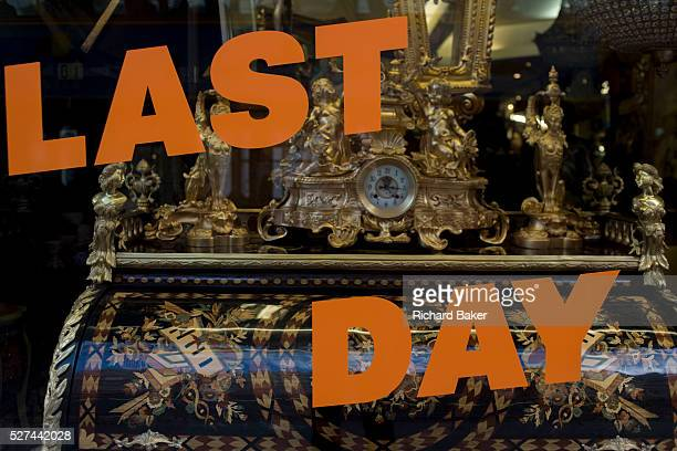 Last day of trading of a Knightsbridge shop selling period furniture in central London The lettering stretches across the window behind which we see...