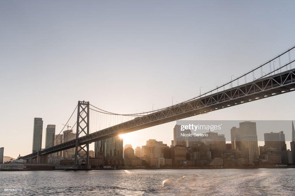 Last ray of sun behind bay bridge from sea : Stock Photo