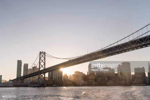 last ray of sun behind bay bridge from sea - bay bridge stock pictures, royalty-free photos & images