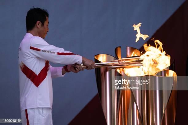 Last torch bearer of Day 1, aerobatics pilot Yoshihide Muroya lights the cauldron at Hibarigahara field during the Tokyo Olympic Games torch relay on...