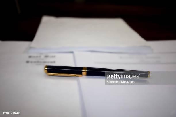 last will & testament & other estate planning documents on wooden desk under pen - uitvaartcentrum stockfoto's en -beelden