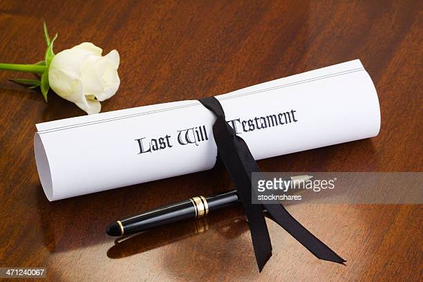 Last will, white rose and black pen sitting on a table
