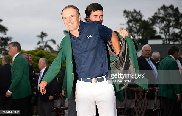 Last years champion Bubba Watson helps Jordan Spieth put on the Green Jacket of the 2015 Masters Champion at the 79th Masters Golf Tournament at...