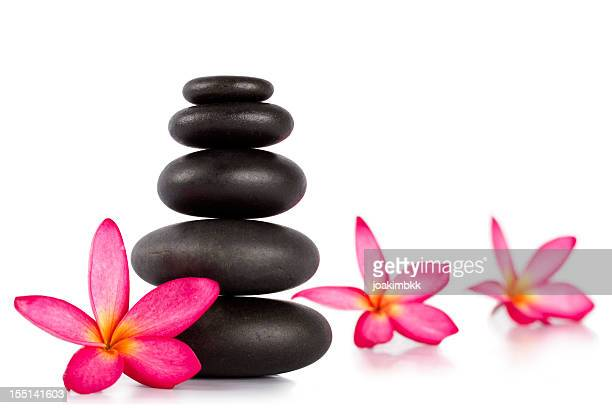 Lastones with frangipani flower for massage therapy isolated on white