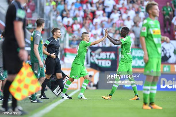 Laszlo Benes and Denis Zakaria of Borussia Moenchengladbach touch hands at their substitution during the Bundesliga match between FC Augsburg and...