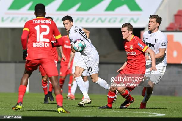 Laszlo Benes and Florian Niederlechner of FC Augsburg and Sven Bender of Leverkusen compete for the ball during the Bundesliga match between FC...