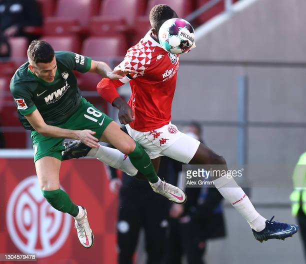 Laszlo Benes of Augsburg is challenged by Moussa Niakhate of Mainz during the Bundesliga match between 1. FSV Mainz 05 and FC Augsburg at Opel Arena...