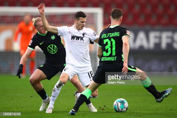 Laszlo Benes of FC Augsburg is challenged by Xaver Schlager and Yannick Gerhardt of VfL Wolfsburg during the Bundesliga match between FC Augsburg and...