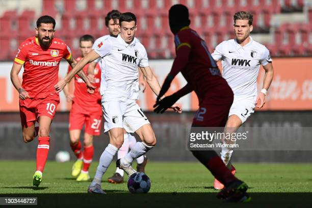Laszlo Benes of FC Augsburg plays the ball as Kerem Demirbay of Leverkusen and Florian Niederlechner of FC Augsburg run behind him during the...
