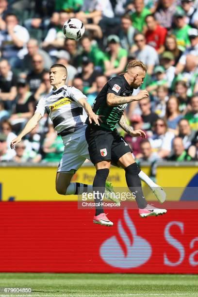 Laszlo Benes of Moenchengladbach and Jonathan Schmid of Augsburg go up for a header during the Bundesliga match between Borussia Moenchengladbach and...