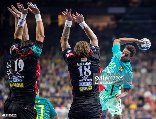 Laszlo Nagy and Andreas Nilsson of Veszprem try to stop Wael Jallouz of Barcelona during the VELUX EHF FINAL4 3rd place match between Telekom...
