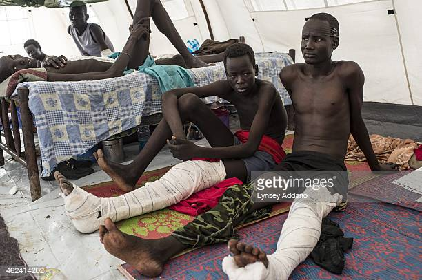 Lat Magai center a Nuer soldier with the opposition army sits alongside other injured opposition soldiers at a tent hospital at the base of the...