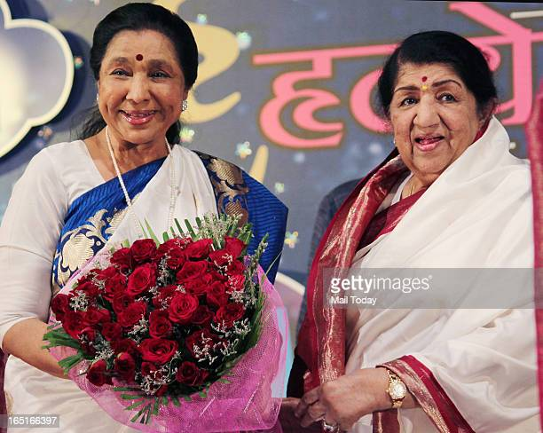 Lata Mangeshkar and her sister Asha Bhosle during the Pandit Hridaynath Mangeshkar Awards in Mumbai on March 31 2013