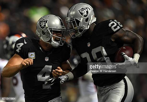 Latavius Murray and Derek Carr of the Oakland Raiders celebrate after a touchdown against the Denver Broncos at OaklandAlameda County Coliseum on...