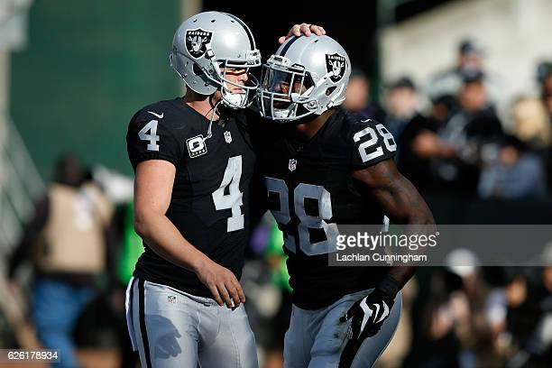 Latavius Murray and Derek Carr of the Oakland Raiders celebrate after a touchdown against the Carolina Panthers during their NFL game on November 27...