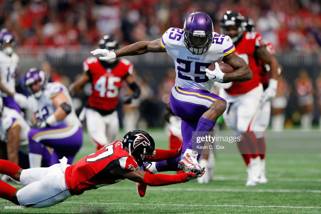 Latavius Murray #25 of the Minnesota Vikings avoids the tackle by Damontae Kazee #27 of the Atlanta Falcons on a long run during the first half at Mercedes-Benz Stadium on December 3, 2017 in Atlanta, Georgia.